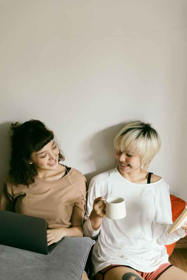cheerful sisters with cup of drink using laptop on floor